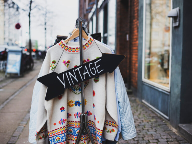 Vintage,Sign,With,A,Background,Of,Different,Vintage,Clothing,On