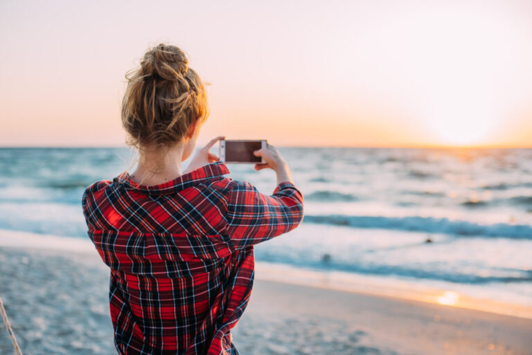 Young,Woman,Taking,Photos,With,Her,Smartphone,On,Beach,During